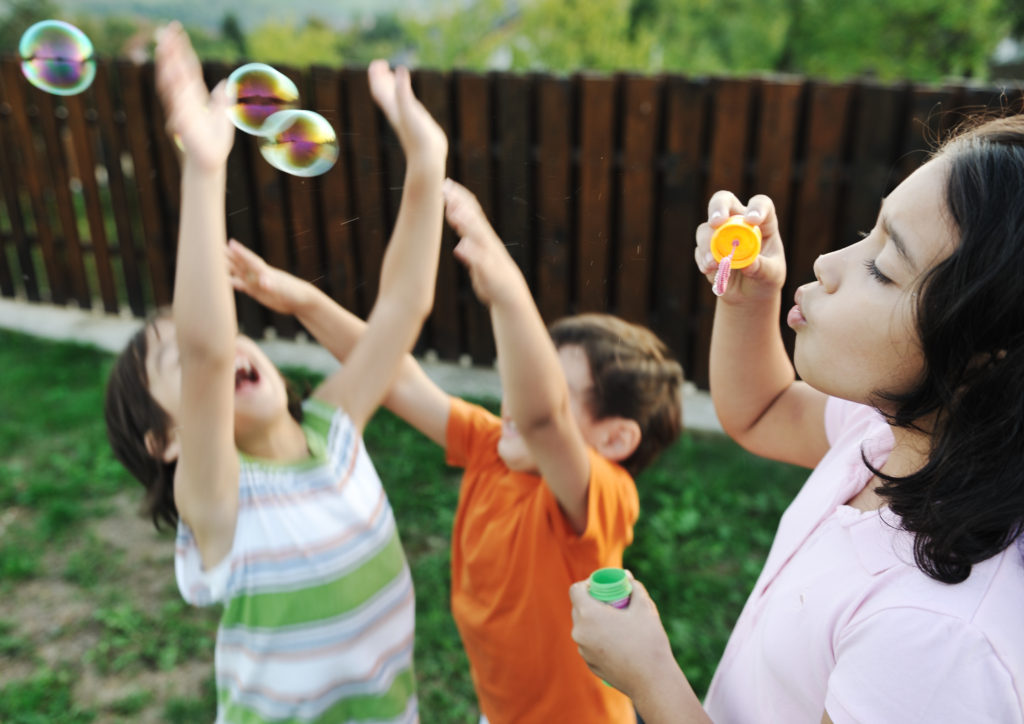 Children blowing bubbles; housing policies that harm people with records harm people of color